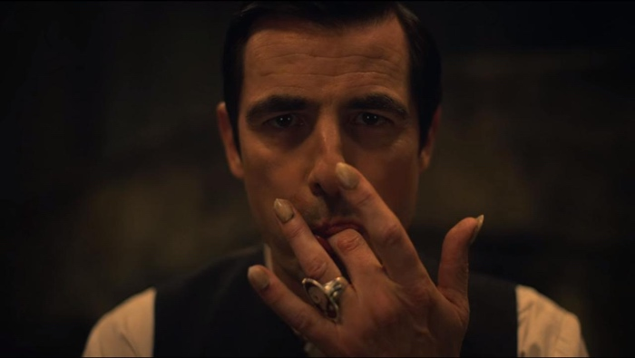 Count Dracula licking his fingers in Dracula mini-series 2020