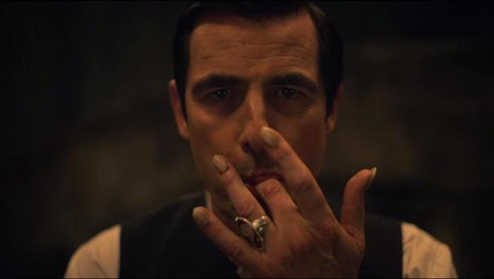 Count Dracula licking his fingers in Dracula mini-series 2020