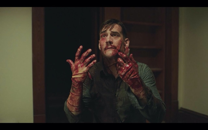 Bloodied Don Koch begging for his life in Girl on the Third Floor 2019