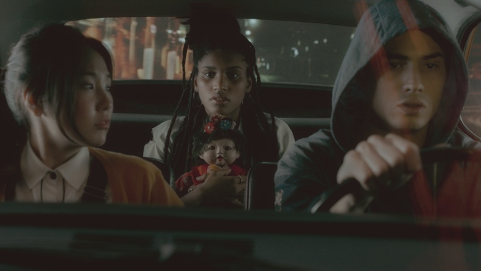Mila, Carla holding the porcelain doll and Pardal driving in a car in Spectros season 1