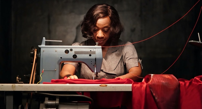 Sheila sowing her own red dress in In Fabric 2018