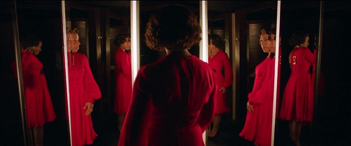 Sheila admiring herself in the mirror with her new red dress in In Fabric 2018