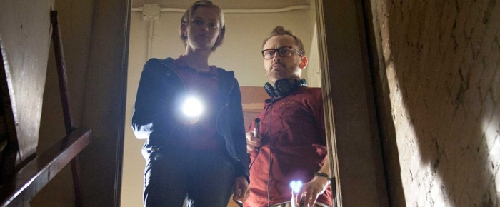Claire and Luke staring down the basement in The Innkeepers 2011