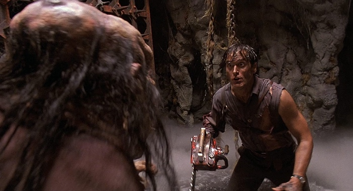 Ash fighting a big Deadite in the pit in Army of Darkness 1992