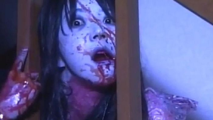 Kayako on the stairs looking through the banister in Ju-on The Curse 2 2000