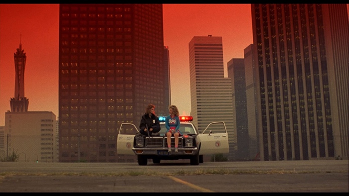 Reggie and Sam sitting on the hood of a police car in Night of the Comet 1984