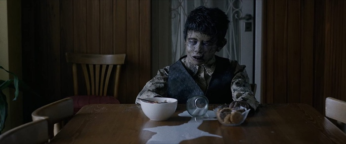 Dead zombie boy sitting at the table in Aterrados/Terrified 2017