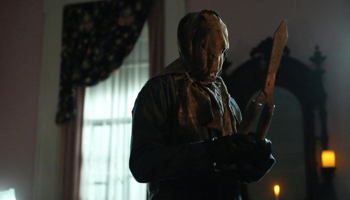 The Killer wearing an Anna Hobbs mask and holds garden shears in Scream season 2 Halloween Special