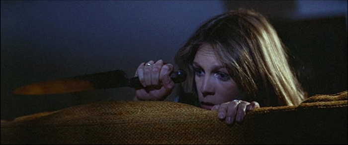Laurie Strode hiding behind the couch with a knife in Halloween 1978